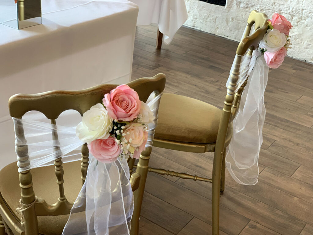bride & groom ceremony chair with flowers and sash